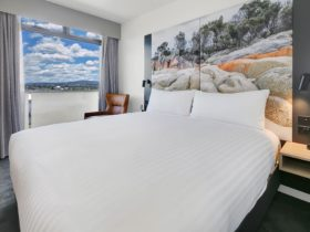 Hotel room, king bed with white linen, large picture headboard, and window with sky view.