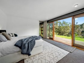 Master bedroom has an adjoining deck overlooking the river.