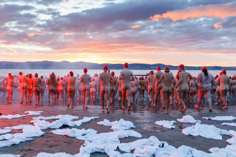 Thousands of people run into the River Derwent at sunrise for Dark Mofo's annual Nude Solstice Swim