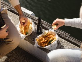 Two people enjoying fish and chips on the side of the dock outside Mures Lower Deck.
