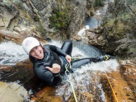 A canyoner about to go over a big waterfall at Cradle Mountain, Tasmania