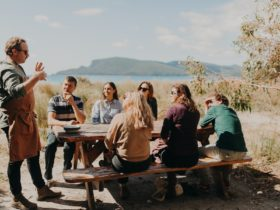 Tour guide and chef stands explaining food and context to group on picnic table. Scenic background.
