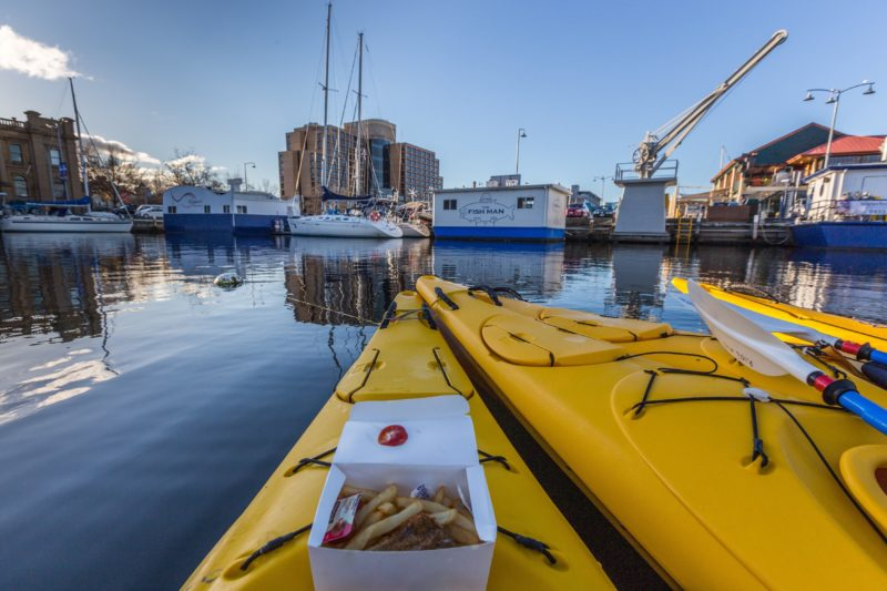 Kayaks in Hobart Docks with fish and chips on the deck of the kayak