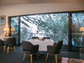 Dining setting in the bar lounge room with view from the balcony towards the mountani