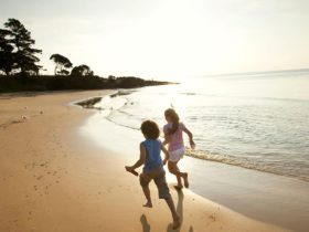 Two young kids running along the beach in Phillip Island