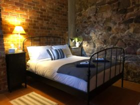 Gorgeous bedroom with vintage queen bed with feature Rock wall built during the Gold Rush in 1800's