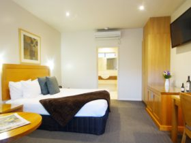 An intimate room featuring a king size bed an ensuite with a corner spa