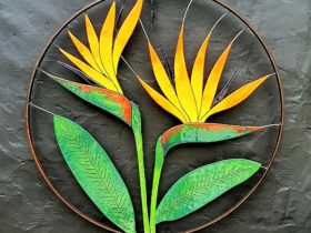Round metal wall sculpture featuring a bird of paradise made of slumped enamelled glass