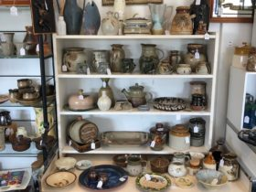 Large collection of pottery by different artists.