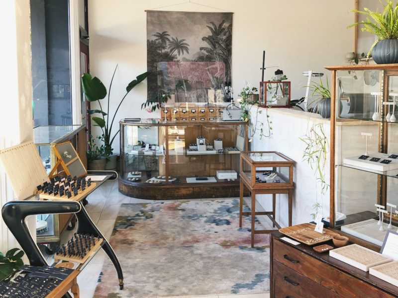 A photo of a shop interior with a large rug on marble floors with vintage wood and glass cabinetry