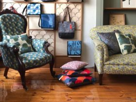 upholstered chair and lounge with bright cushions on wooden floor and handbags hanging behind