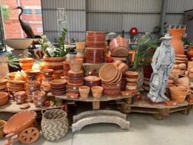 section of garden warehouse with stacks of terracotta pots on floor and glass tables