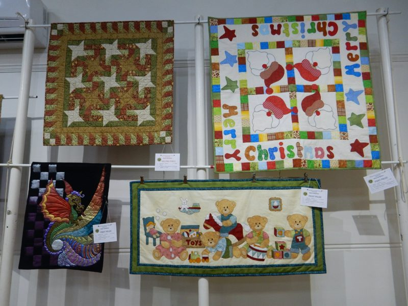 Four patchwork and applique quilts, with stars, Santas, dragon and teddies