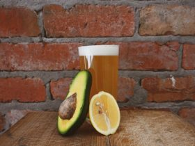 A pot of beer in front of a brick wall with half an avocado and half a lemon in front of it