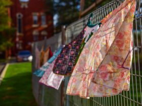 Colourful aprons strung together along a fence, moving gently with the wind