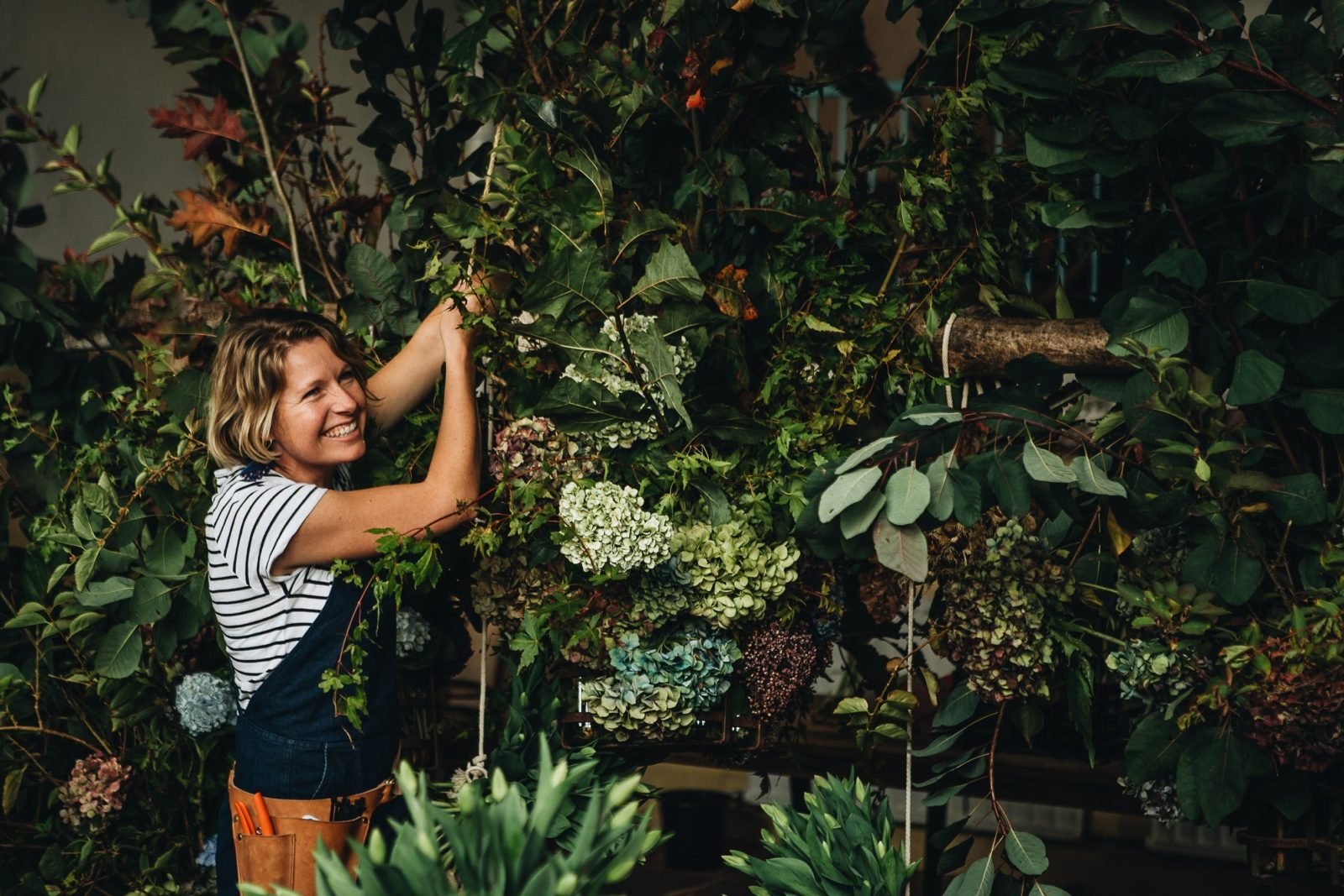 Female florist at work, smiling, surrounded by plants and flowers