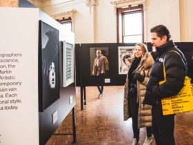 Biennale Exhibition with two visitors looking at portrait