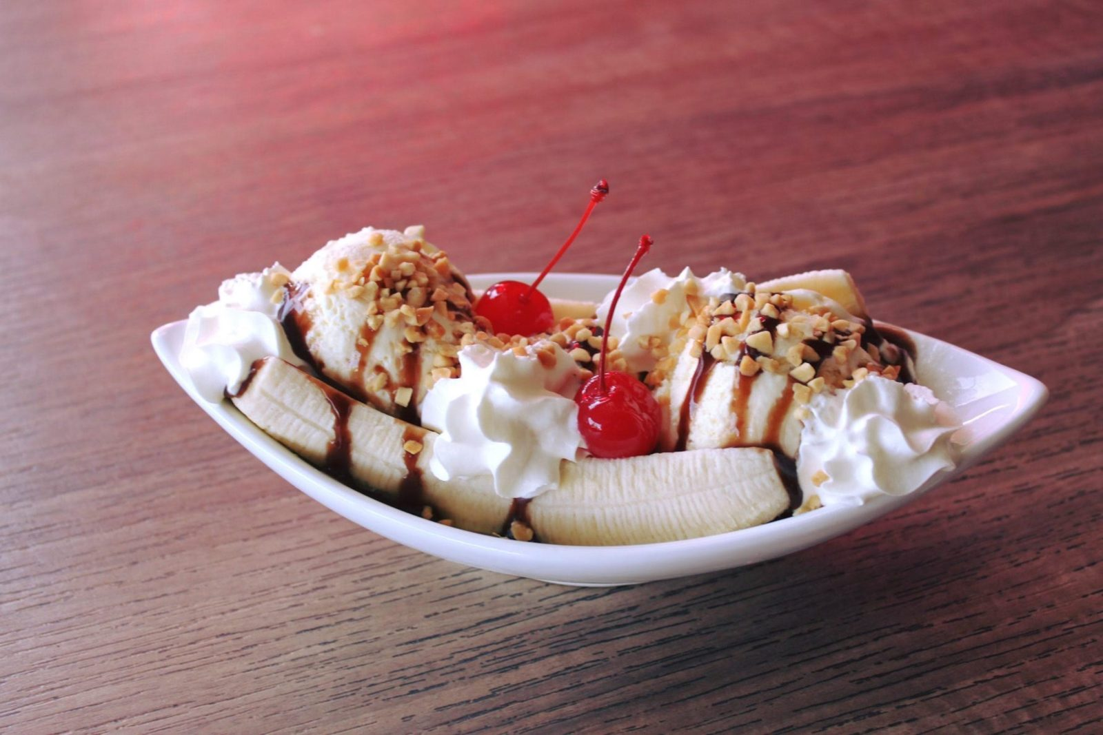 fresh bananas covered in whipped cream, ice-cream, nuts and cherries in a ice-cream boat dish