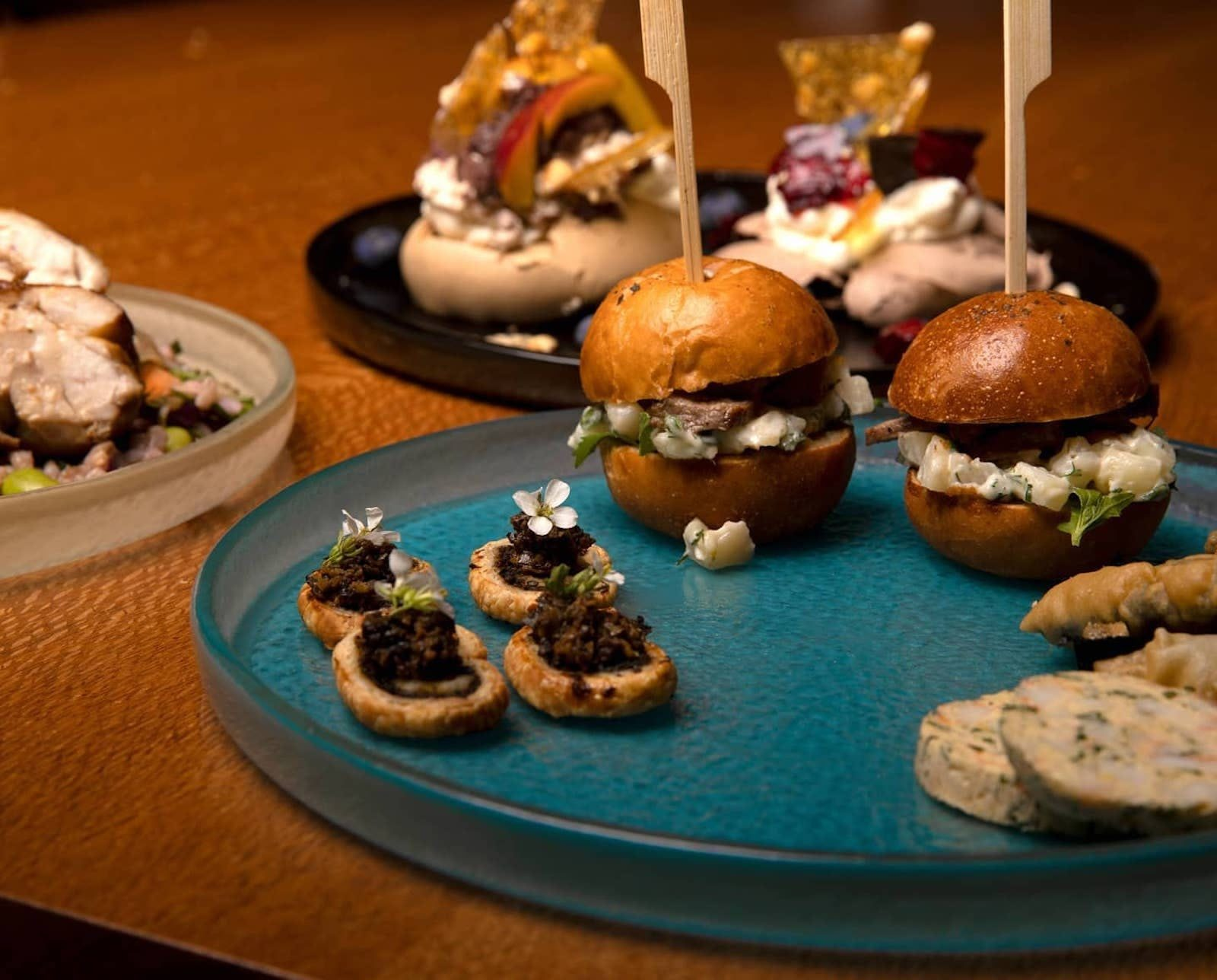 mini burgers and appetisers on teal plate