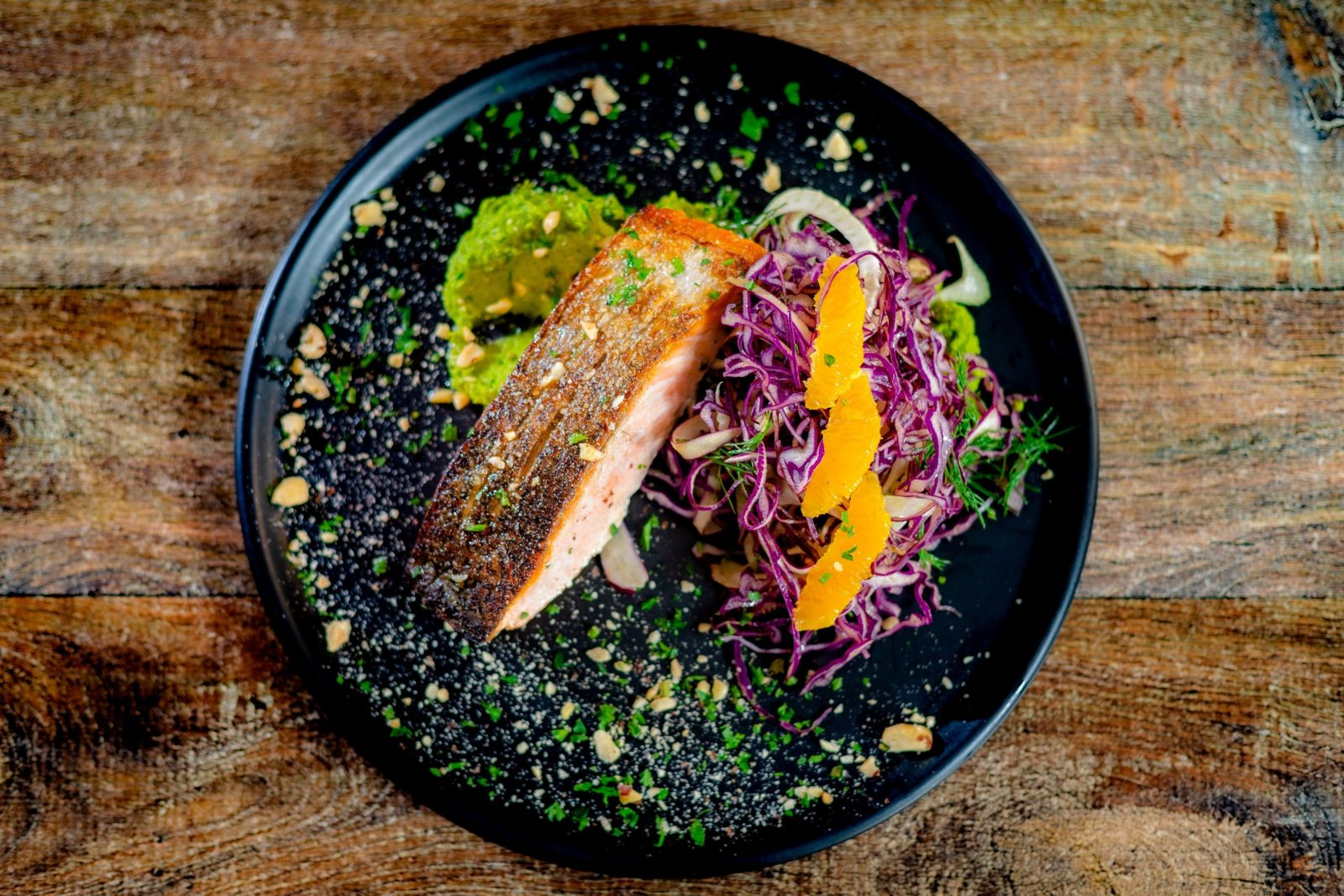 aerial shot of pan-fried salmon on shredded purple cabbage sitting on black plate