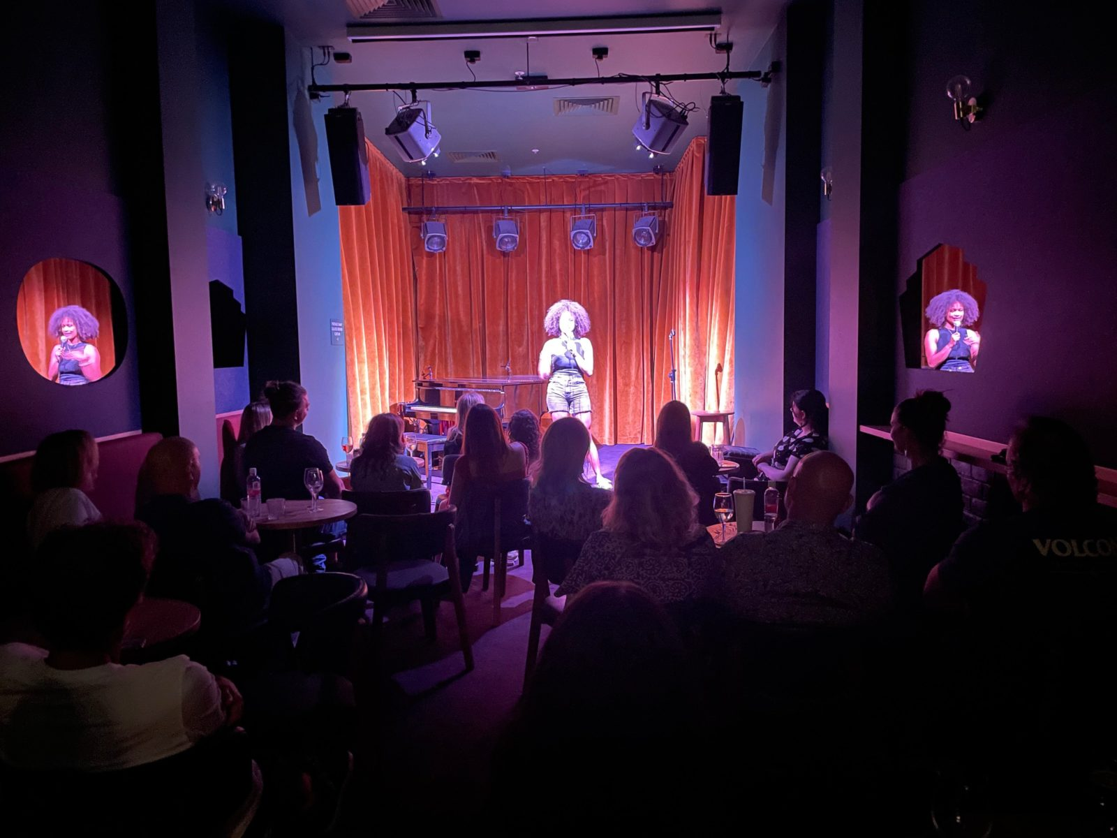 A photo of a women performing stand up comedy to a full house