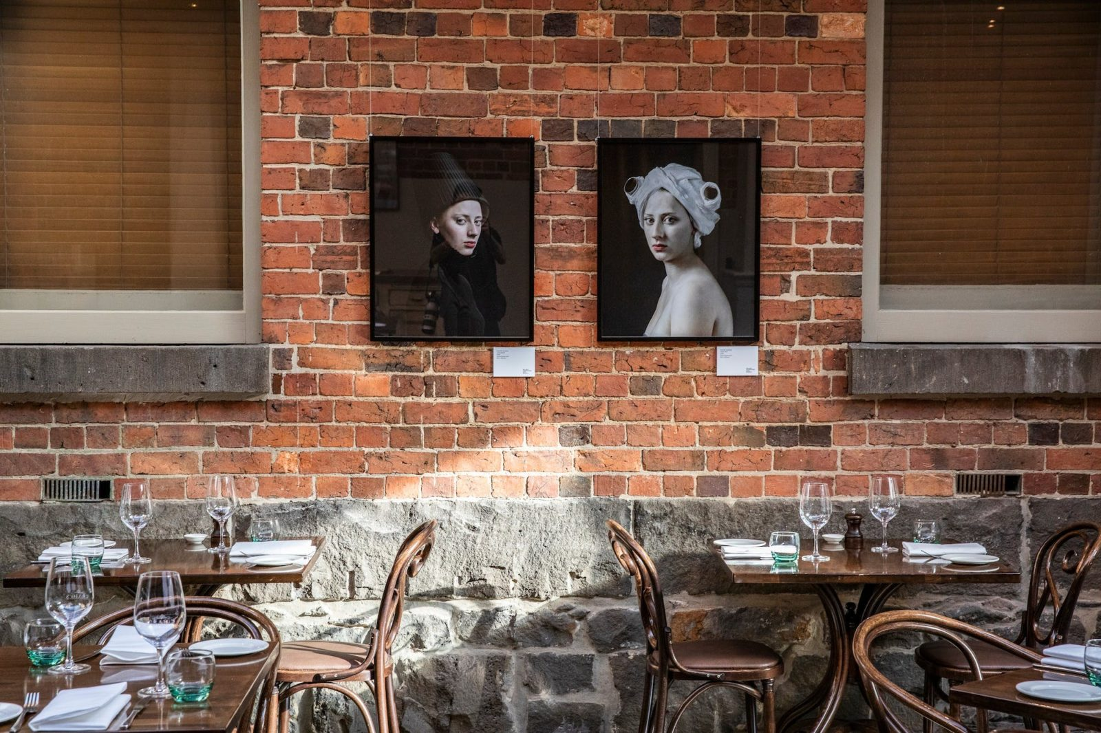 two tables in front of exposed brick wall with two portraits hanging
