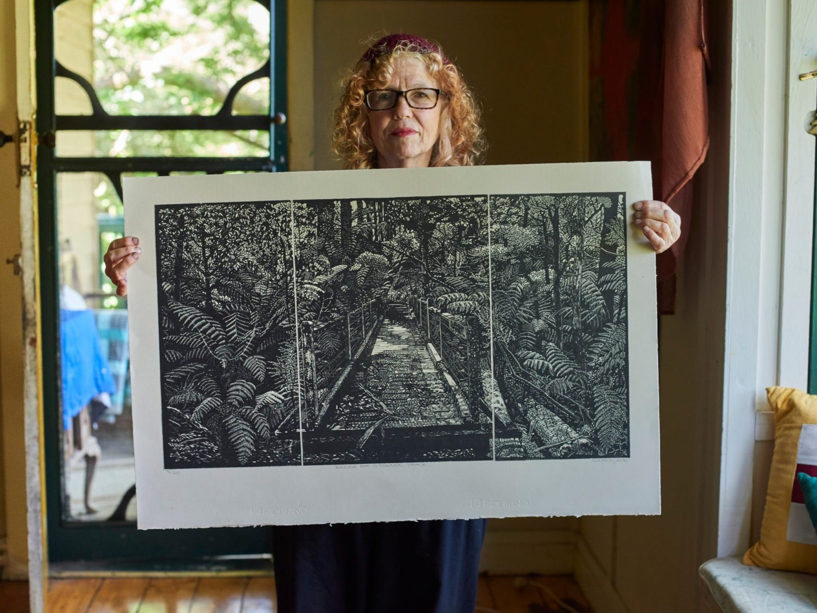 Artist Chris Lawry holding one of her printed works