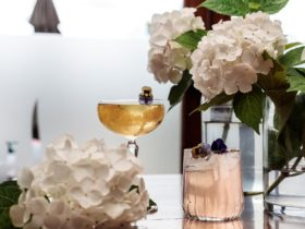 two cocktails on table surrounded by white hydrangeas