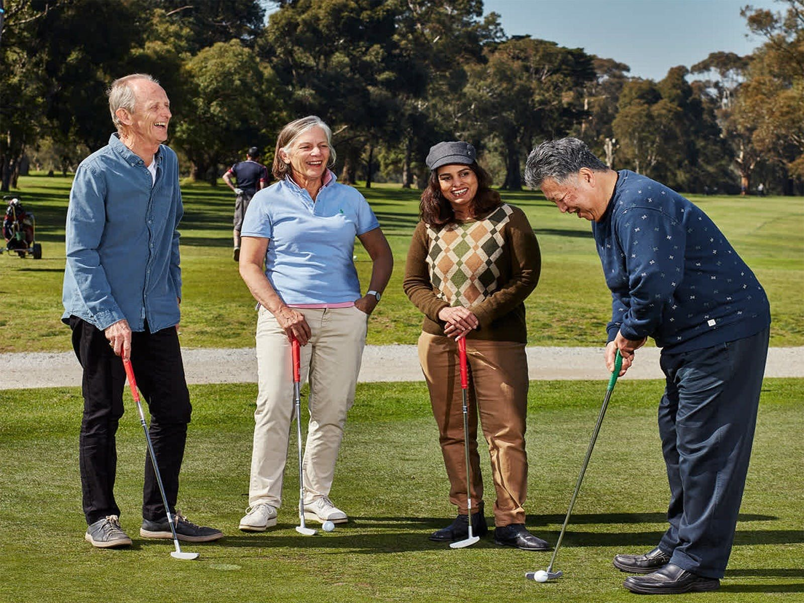4 people on a golf green with golf clubs