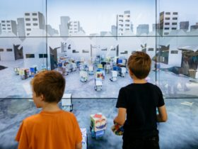 Two young boys looking at a digital artwork containing a city landscape/