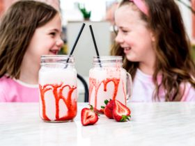 two strawberry milkshakes in glass jars with strawberry drizzle with two young girls giggling behind