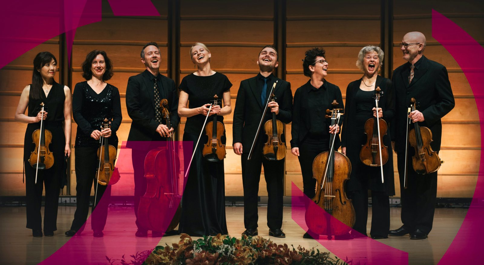 Musicians from the the Australian Romantic & Classical Orchestra, standing on stage and laughing.