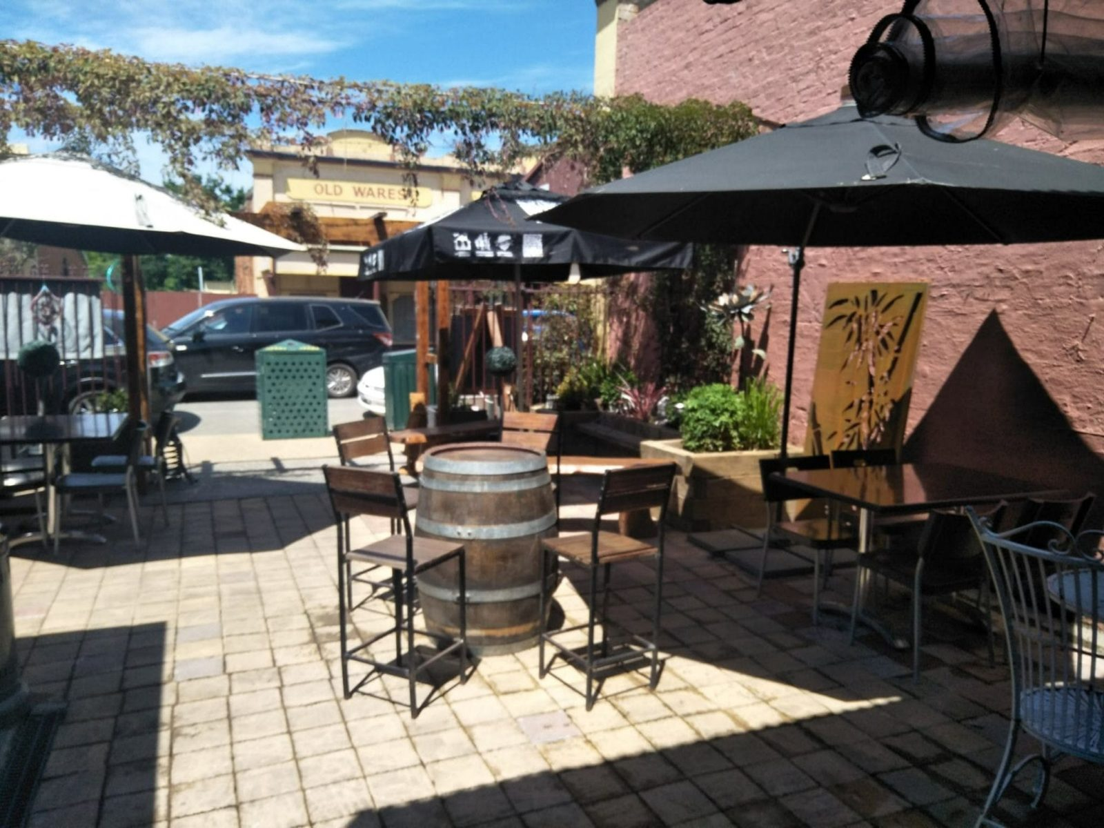 Sunny day in the courtyard, high bar stools around wine barrel table, red brick wall behind