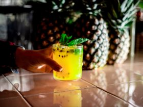 yellow caipirinha cocktail in hand in front of pineapples