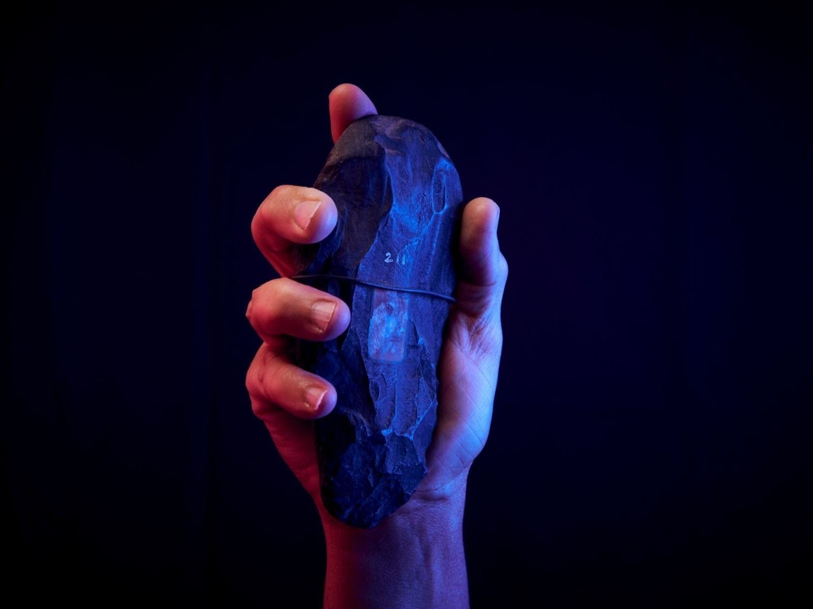 A hand holds a stone