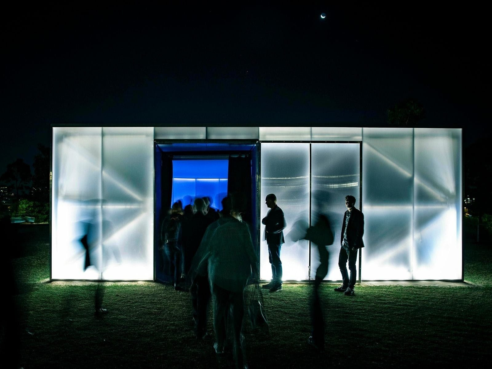 Shadowy people enter an illuminated box in a garden.
