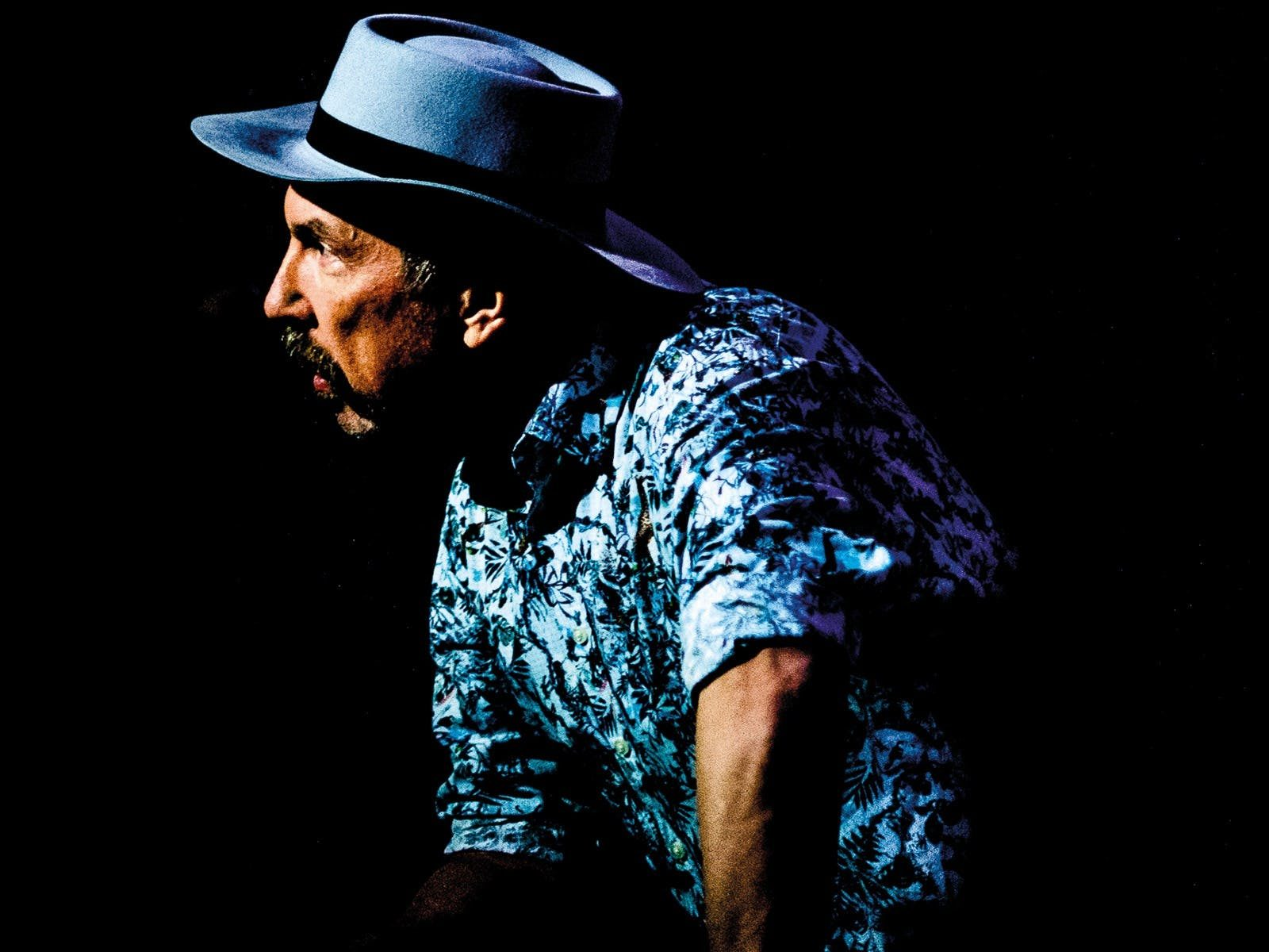Side profile of man wearing blue shirt and hat