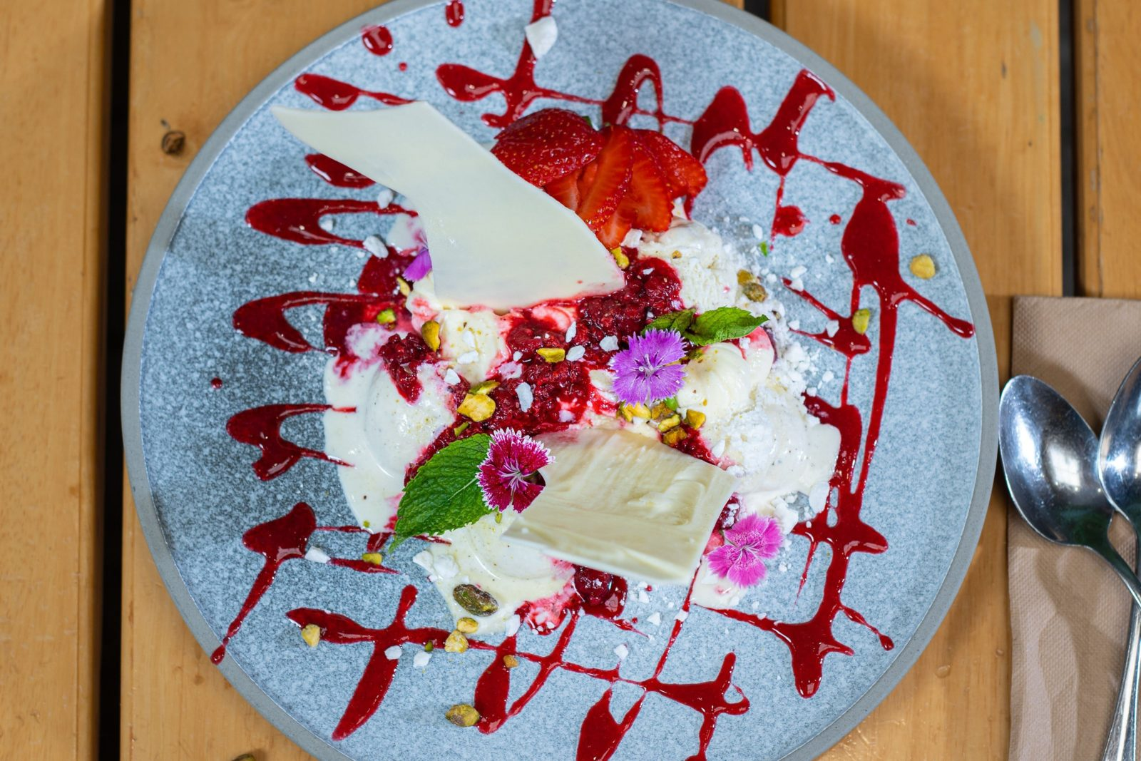 aerial shot of plate with vanilla ice cream, raspberry drizzle, meringue shards and purple flower