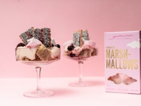 Two iced vovo trifle with sponge roll, jelly and marshmallows in glass cups against pink background