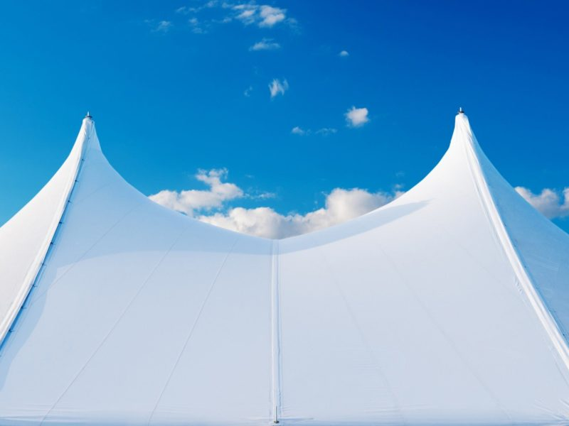 Image is of a white big top tent in he foreground with bright blue sky and low cloud in background.