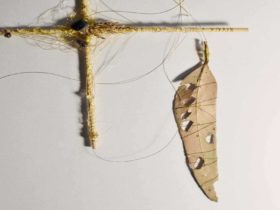 Photograph is of a cross made of twig and a dried leaf eaten by insects, combine by a fine thread