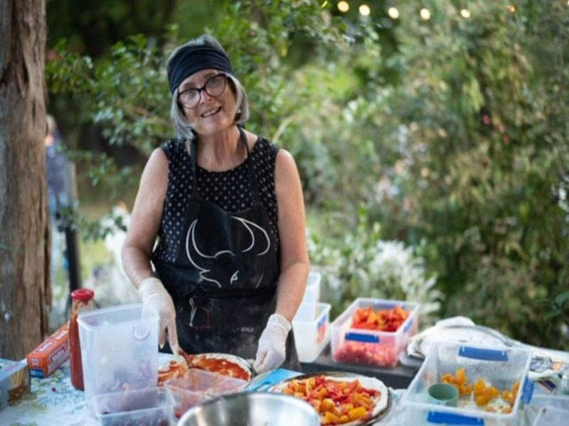 Smiling lady preparing pizza with lush garden behind her