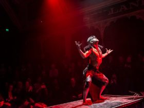 A dancer on a stage lit with red lights, with their back to the audience, at YIRRAMBOI 2019