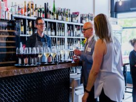 Guests talk at the bar over a glass of wine