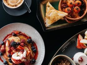 Aerial photo of coffee, strawberry and blueberry pancakes and baked eggs with tomatoes and toast