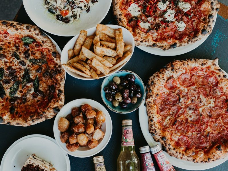 A table at Cugini's laid with woodfired pizzas, pasta, sfingi, olives and drinks.