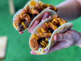Grilled Scotch Fillet and Popcorn Shrimp in soft shell tacos with yellow sauce on top being held