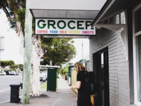 A customer waiting outside the corner store underneath a large sign that says 'GROCER'