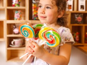 Little girl with brown curly hair holding three large rainbow swirl lollipops