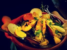 Arms holding spanish dish of seafood, herbs and lemon in a red dish